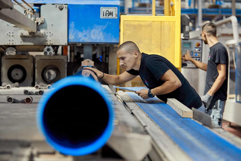 Fotografo industriale in reportage fotografico aziendale produzione tubi e operai tubazioni idriche fognarie.